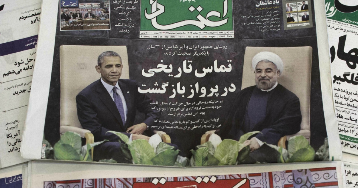 A picture taken on September 28, 2013 in Tehran shows a Iranian newspaper with an image of Iranian President Hassan Rouhani and U.S. President Barack Obama.</p>
