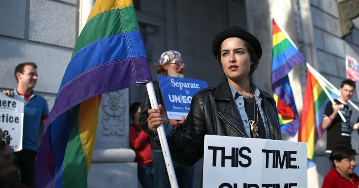 A same-sex marriage supporter holds a pride flag during a rally in support of marriage equality on March 26, 2013 in San Francisco, California.</p>