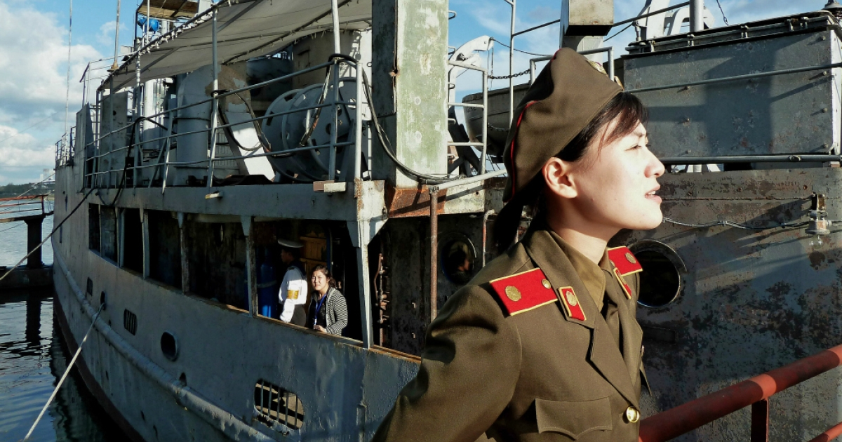 This photo taken on September 22, 2010 shows a North Korean military female guide speaking to some visitors next to the captured USS Pueblo docked at a port in Pyongyang.</p>