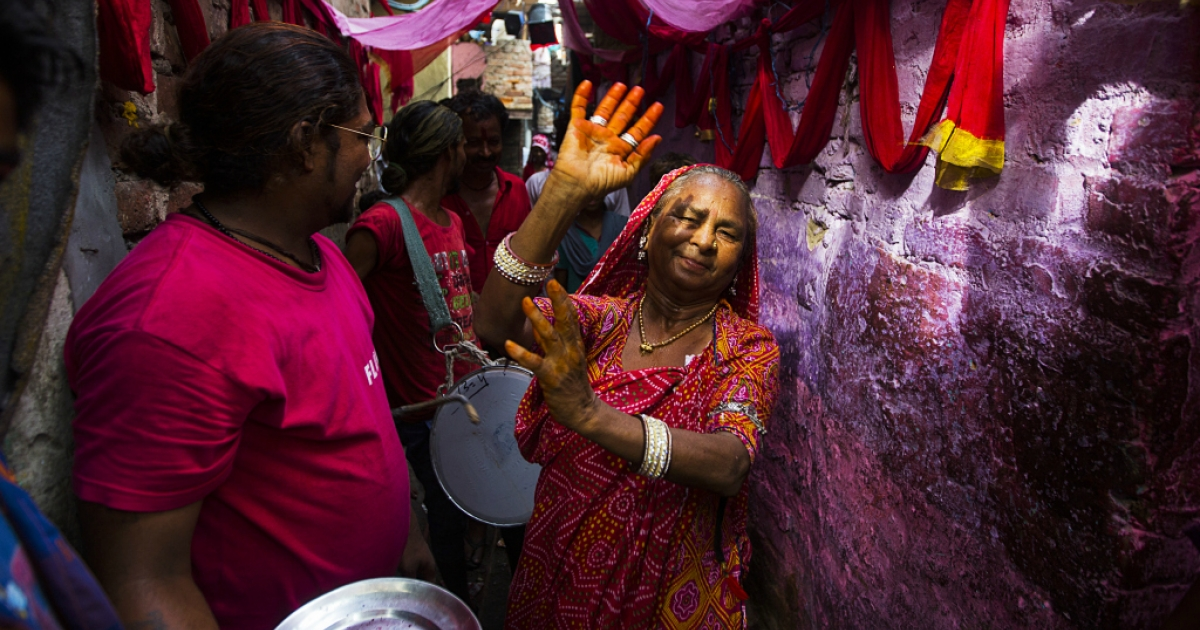 An Indian resident dances down an alleyway in front of drummers during a wedding procession in Kathputli Colony in New Delhi on June 7, 2013.</p>