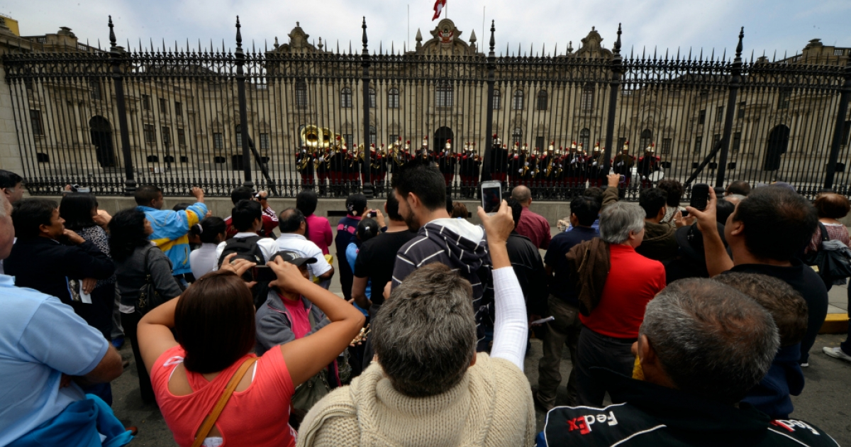 Tourists listen and take pictures of the military band playing in the front patio of the Presidential Palace in Lima on October 31, 2013.</p>
