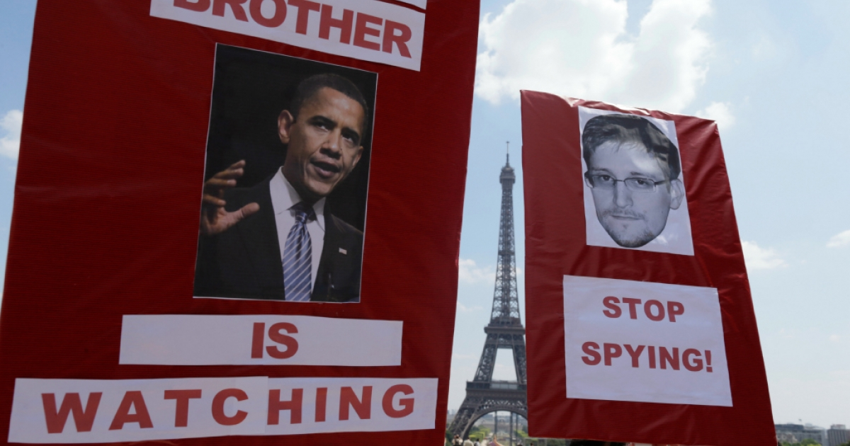 Protesters hold up posters with pictures of US President Barack Obama and Edward Snowden, the former technical contractor of the US Central Intelligence Agency, during a demonstration in support of Snowden at the Place du Trocadero in front of the Eiffel tower in Paris on July 7, 2013.</p>