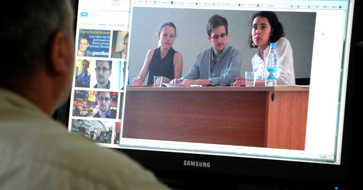 A man looks in Moscow on July 12, 2013, at a computer screen displaying a photo US National Security Agency fugitive leaker Edward Snowden during his meeting with leading Russian rights activists and lawyers at Moscow's Sheremetyevo airport.</p>