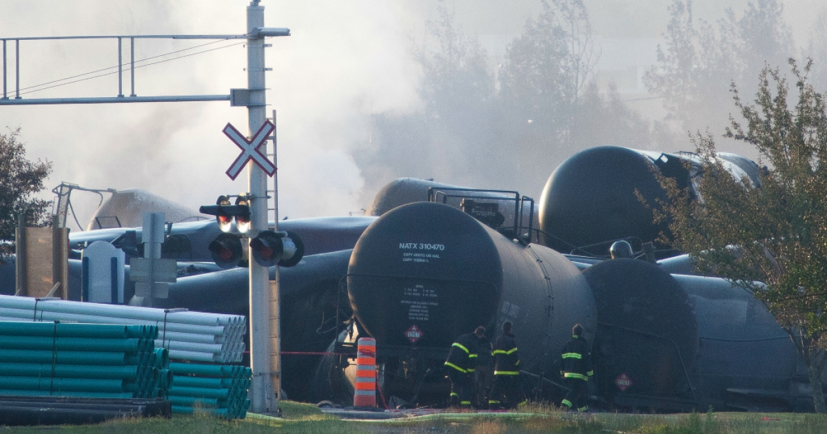 Firefighters inspect the wreckage on July 7, 2013 of a freight train loaded with oil that derailed the day before in Lac-Megantic in Canada's Quebec province, sparking explosions that engulfed about 30 buildings in a wall of fire.</p>