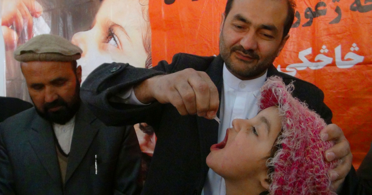An Afghan health worker administers polio vaccine drops to a child during the first day of a vaccination campaign in Jalalabad, Nangarhar province on December 29, 2013. Polio, once a worldwide scourge, is endemic in just three countries now - Afghanistan, Nigeria and Pakistan.</p>