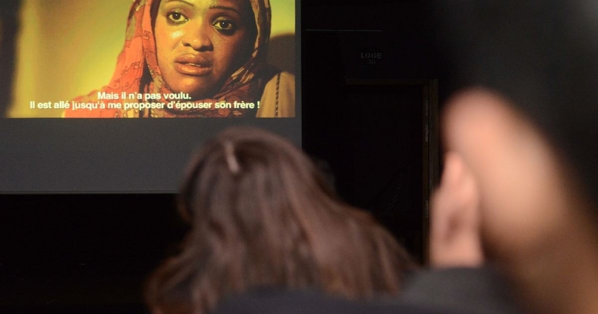 An audience watch a documentary entitled