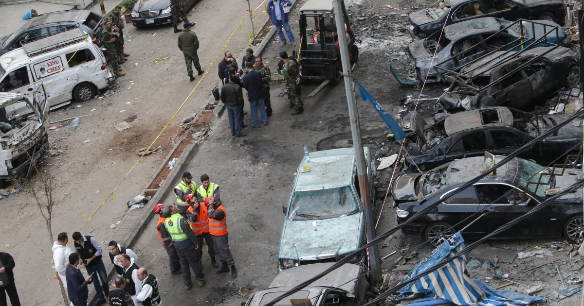 Lebanese security forces and forensic experts gather at the site of an explosion in the Haret Hreik neighborhood in southern Beirut on January 22, 2014.</p>