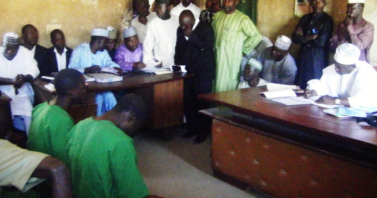 A picture taken on January 22, 2014 shows two suspected homosexuals in green prison uniforms (L) sitting before Judge El-Yakubu Aliyu during court proceedings at Unguwar Jaki Upper Sharia Court in the northern Nigerian city of Bauchi. Two Islamic courts in northern Nigeria have been forced to suspend the trials of 10 men accused of homosexuality because of fears of mob violence, judges and officials have said on January 29. An angry crowd last week pelted stones at seven men suspected of breaking Islamic law banning homosexuality after their hearing was adjourned at the Unguwar Jaki Upper Sharia Court in Bauchi.</p>
