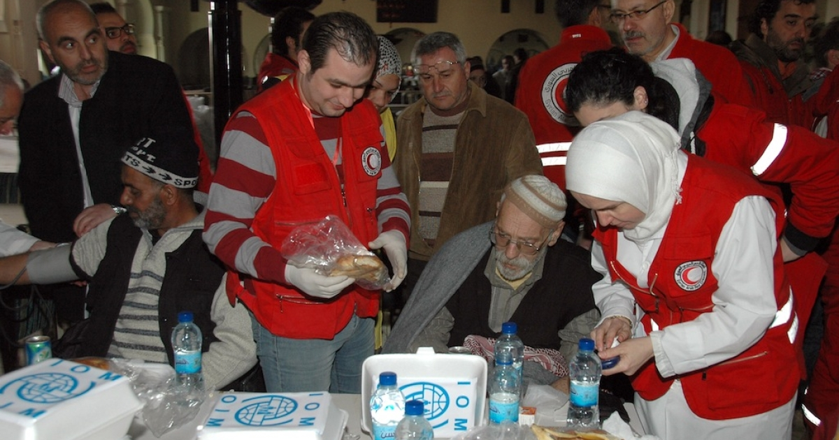 Syrians receive food and medical aid from Syrian Red Crescent workers upon their arrival in regime-held areas of the Syrian city of Homs on February 7, 2014, after more than a dozen civilians were evacuated from the rebel-held areas under a UN-supervised deal between the Syrian government and opposition.</p>