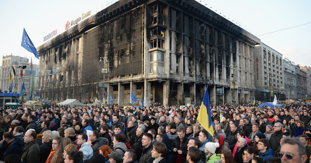 People gather in Independence square in Kiev, Ukraine as coffins of anti-government demonstrators killed in clashes with police arrive in the square on February 21, 2014.</p>