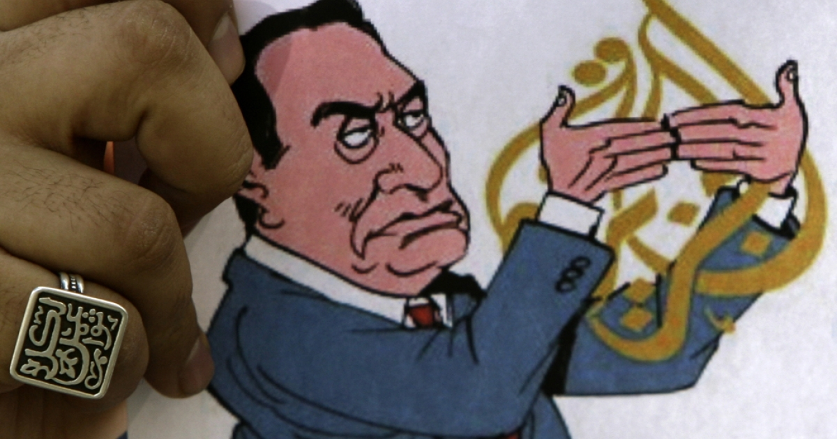 A drawing of former Egyptian President Hosni Mubarak blocking the Al-Jazeera logo during a protest against the closure of its offices in Egypt, Feb. 2, 2011.</p>