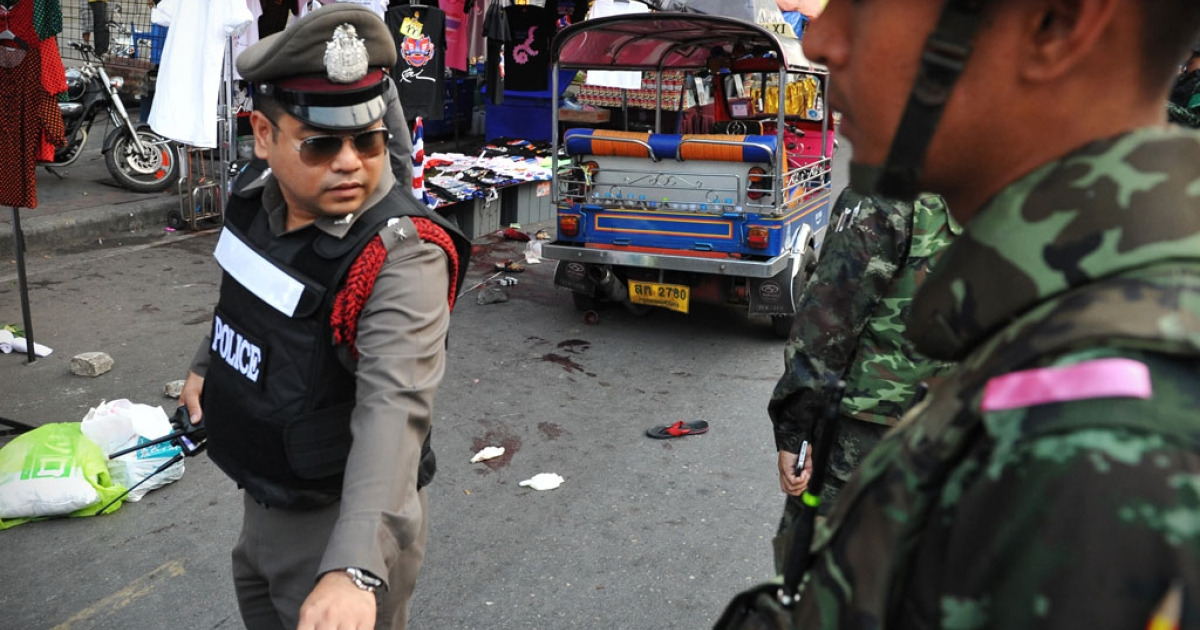 Army soldiers and police stand guard at the scene of a deadly explosion at an anti-government rally on Feb. 23, 2014 in Bangkok, Thailand.</p>