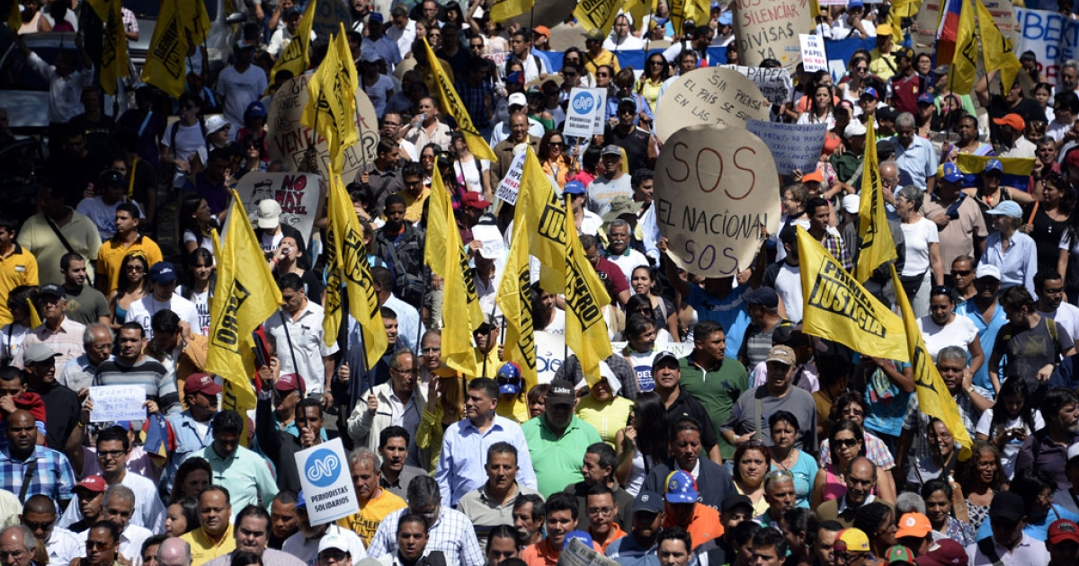 Activists take part in a protest outside the CADIVI headquarters in Caracas on Feb. 11, 2014. About 500 newspaper workers demanded the government release US dollars to buy much-needed newsprint.</p>