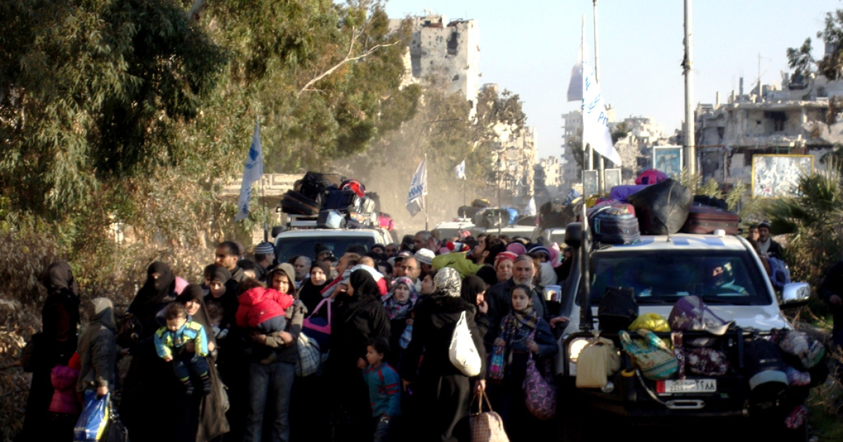 United Nations and Red Crescent vehicles loaded with suitcases escort Syrian civilians evacuated from the besieged Syrian city of Homs, on February 9, 2014.</p>