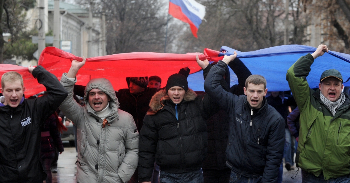 Pro-Moscow demonstrators with a Russian flag near the Crimean parliament building in Simferopol on Thursday.</p>