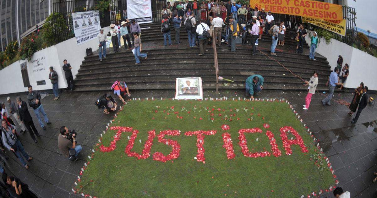 Relatives of the victims of the slaughter of the villa Dos Erres form the word 'Justice' with flowers outside the Supreme Court on Aug. 2, 2011 in Guatemala City before the trial of military men involved.</p>