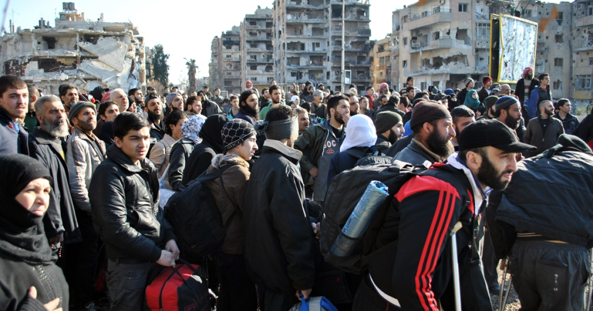 Civilians wait to be evacuated by UN staff, from the besieged Syrian city of Homs, Feb. 9, 2014.</p>