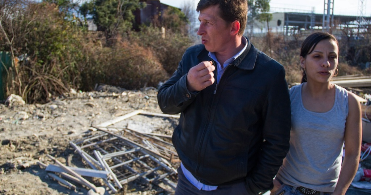 Alexey and Natalya Sdavelyev stand near the site of their former home at their neighbor's property. They were evicted and had their house demolished to make way for a new highway.</p>