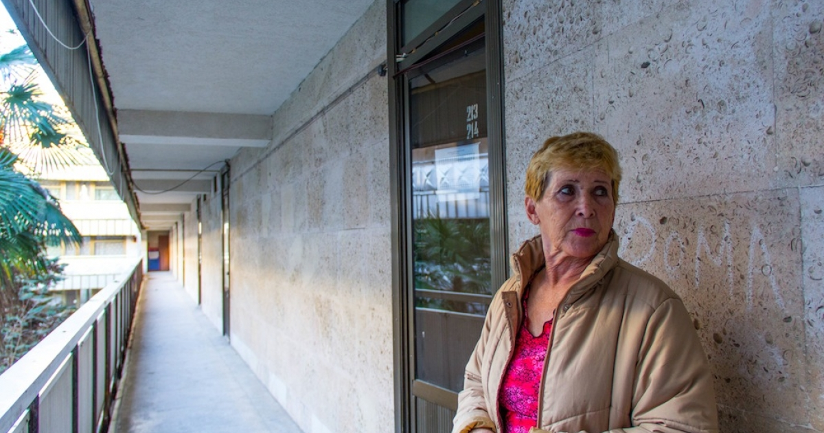 Lyudmila Sdavelyev, 63, stands outside her family's temporary apartment in an inner courtyard in Sochi, Russia. Her family shares a communal kitchen with other residents of the building.</p>