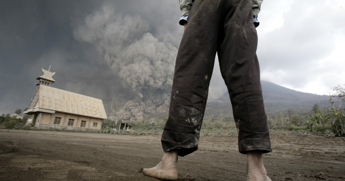 A resident looks on at giant volcanic ash clouds from a village in Karo district during the eruption of Mount Sinabung volcano located in Indonesia's Sumatra island on Feb. 1, 2014.</p>