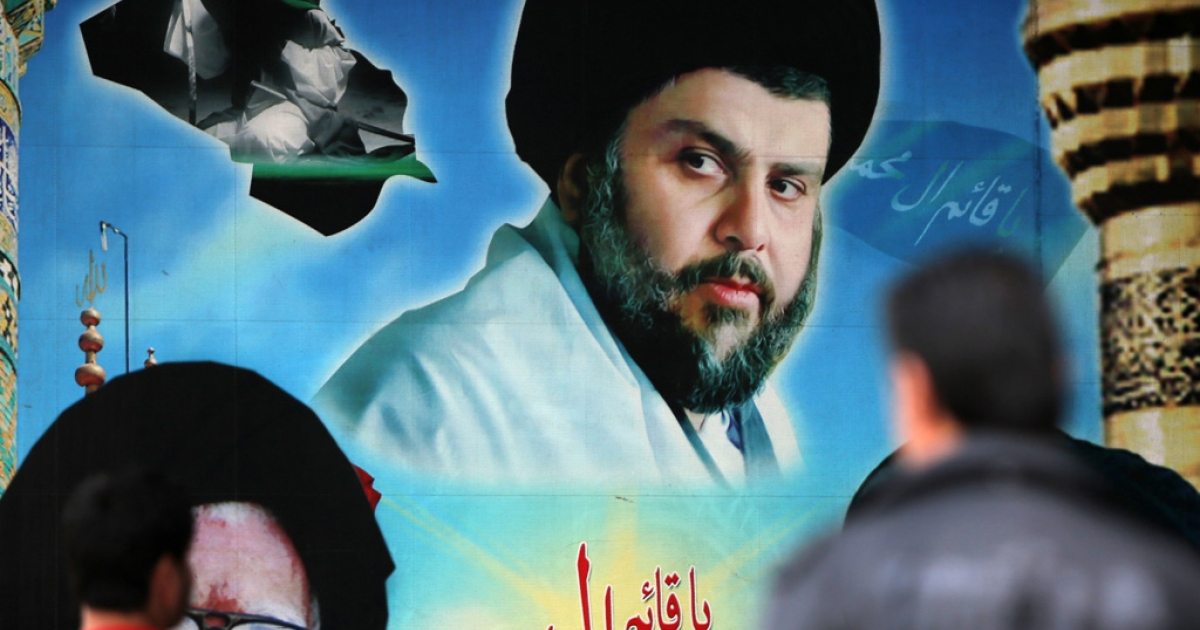 Iraqis walk past a giant portrait of Iraqi Shia cleric Moqtada al-Sadr displayed on February 16, 2014 in Baghdad's Sadr City district.</p>