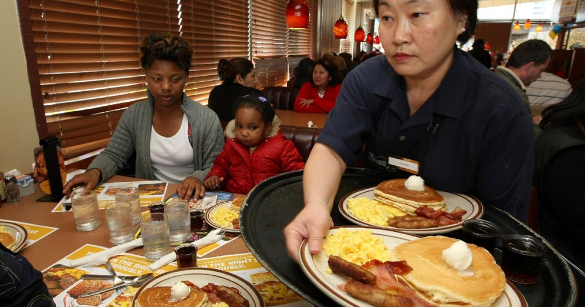 Denny's waitress Fong Van Luben (R) delivers free Grand Slam breakfasts to customers in Emeryville, Calif.</p>