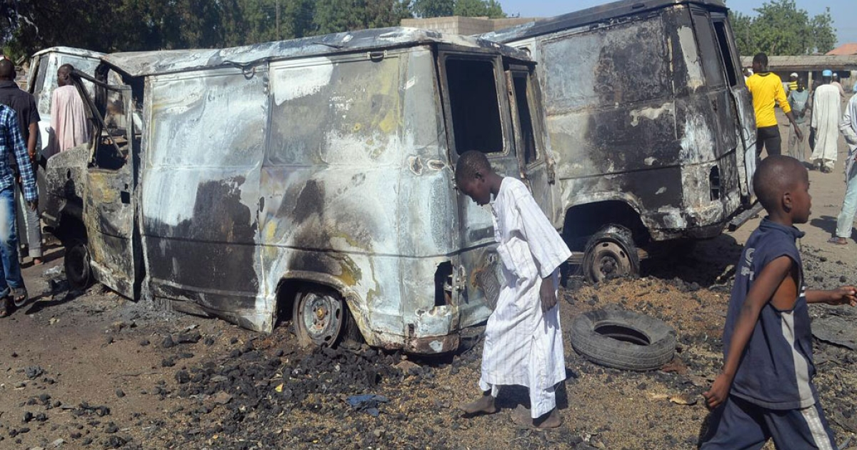 Children stand next to burnt vehicles after an attack by scores of Boko Haram Islamists on Feb. 20, 2014 in the northeast Nigerian town of Bama.</p>