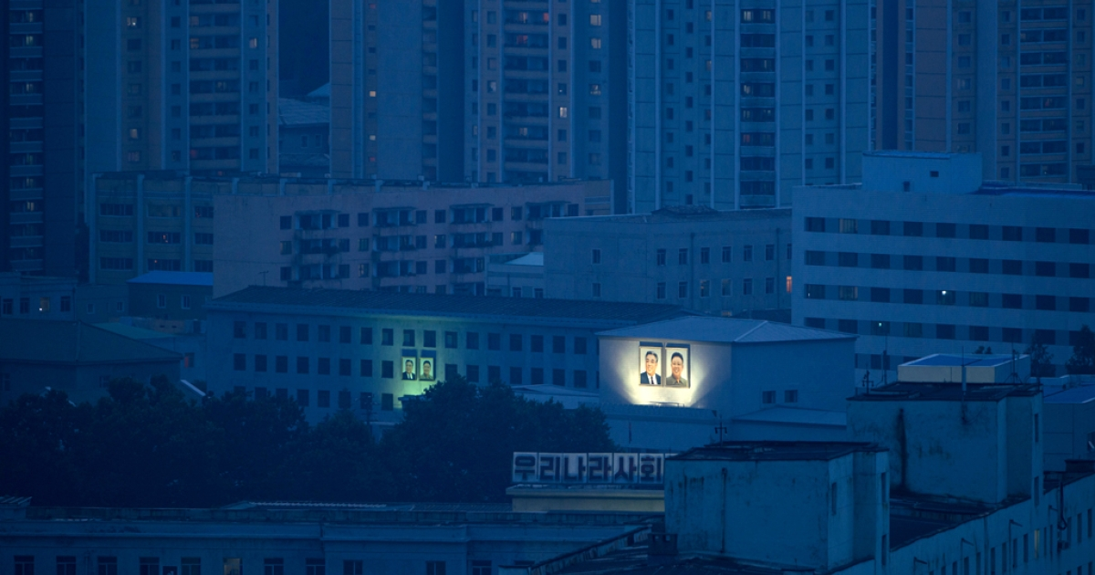 Portraits of former North Korean leaders Kim Il Sung and Kim Jong Il are displayed on buildings of the Pyongyang skyline on July 27, 2013.</p>