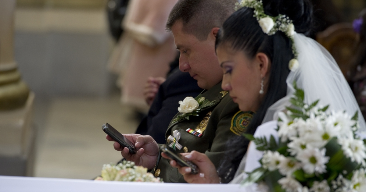 A bride and groom use their mobile phones at the Cathedral of Bogota, Dec. 9, 2011.</p>