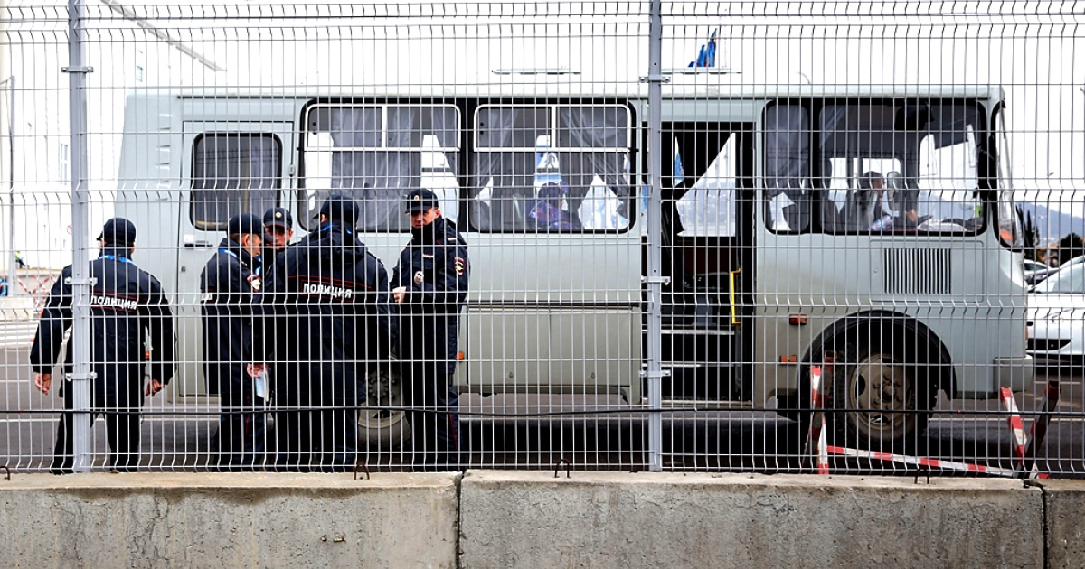 Security officers watch guests across a fence in the Olympic Park during the Sochi 2014 Winter Olympics on February 17, 2014 in Sochi, Russia.</p>
