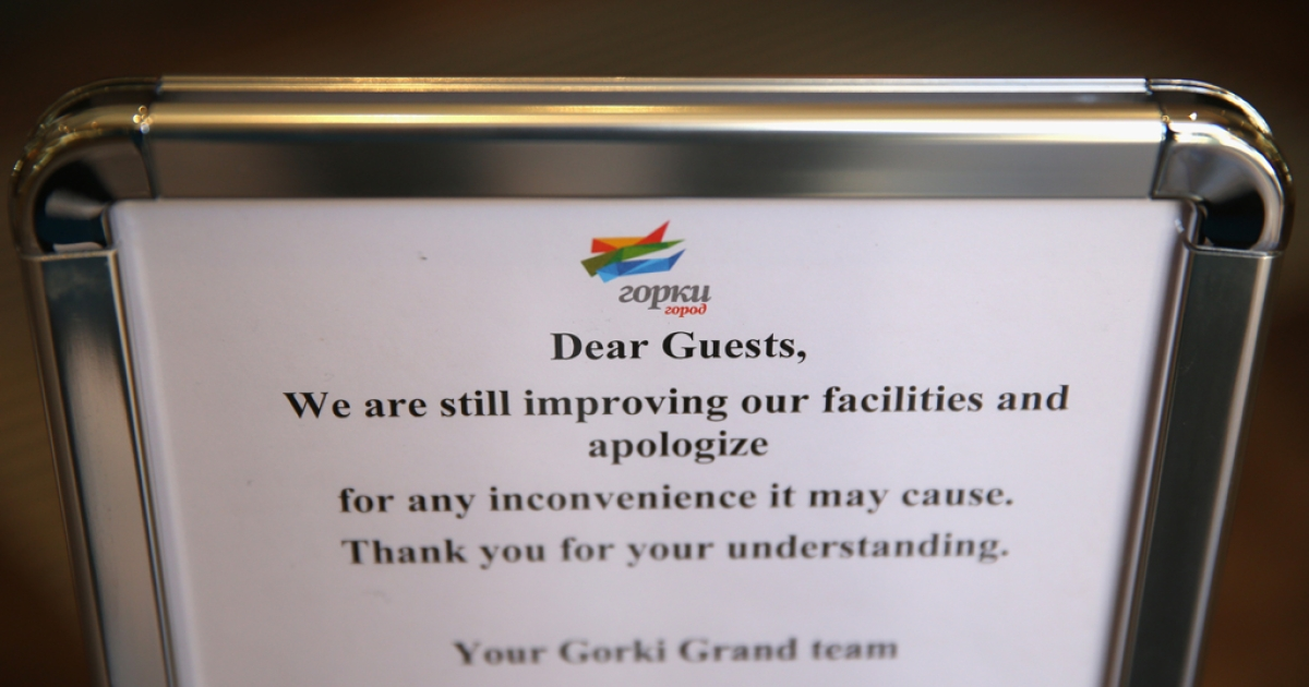 A sign explains the delays related to hotel construction prior to the Sochi 2014 Winter Olympics on Feb. 3, 2014.</p>