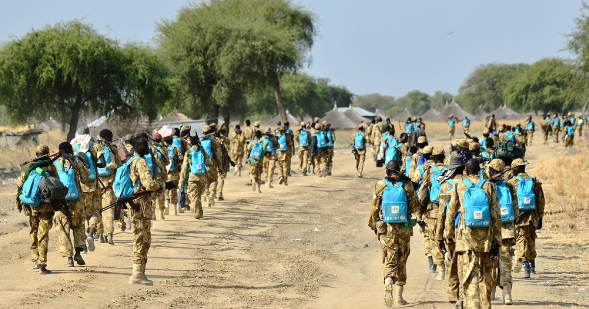 Sudan People's Liberation Army (SPLA) soldiers wearing UNICEF backpacks walk along a road in Mathiang near Bor on January 31, 2014.</p>