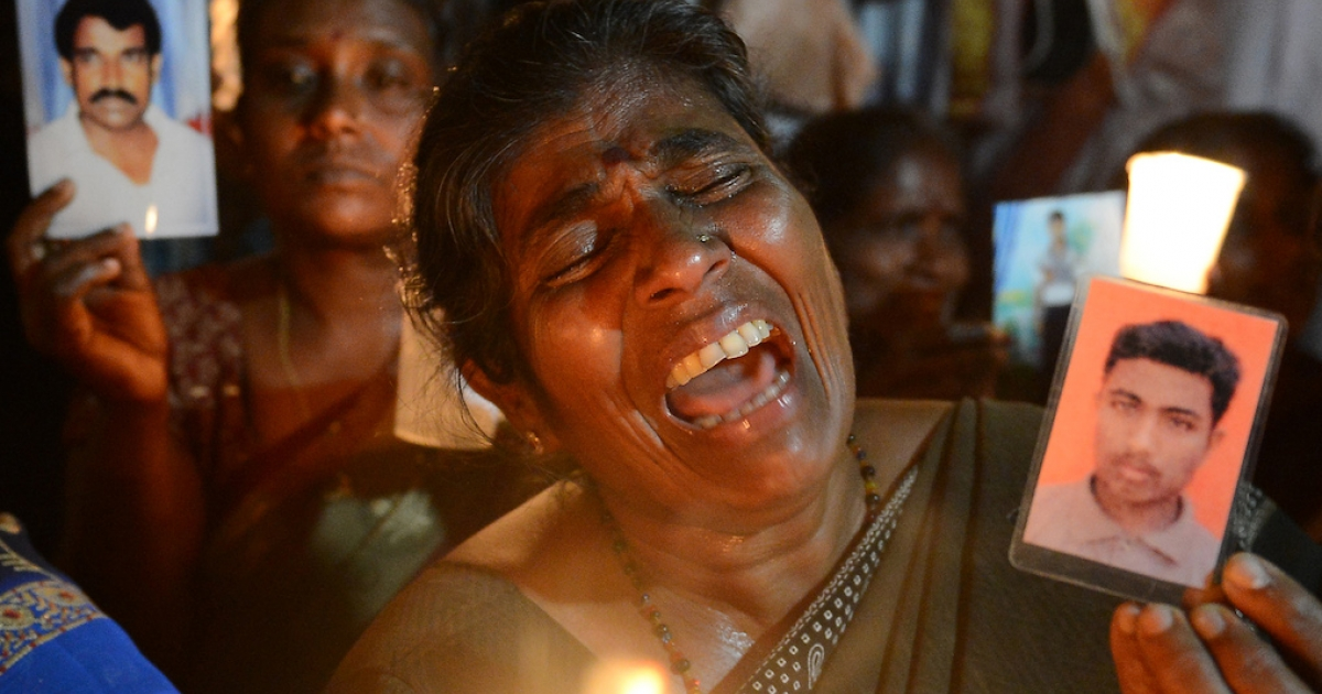 A Sri Lankan activist wails during a candlelight vigil in Colombo on August 30, 2013, held to mark the International Day of the Disappeared. The vigil at Colombo's Independence Square came as UN human rights chief Navi Pillay visited the island to probe alleged war crimes. Some of the alleged sites have been transformed into tourist attractions for the victors.</p>