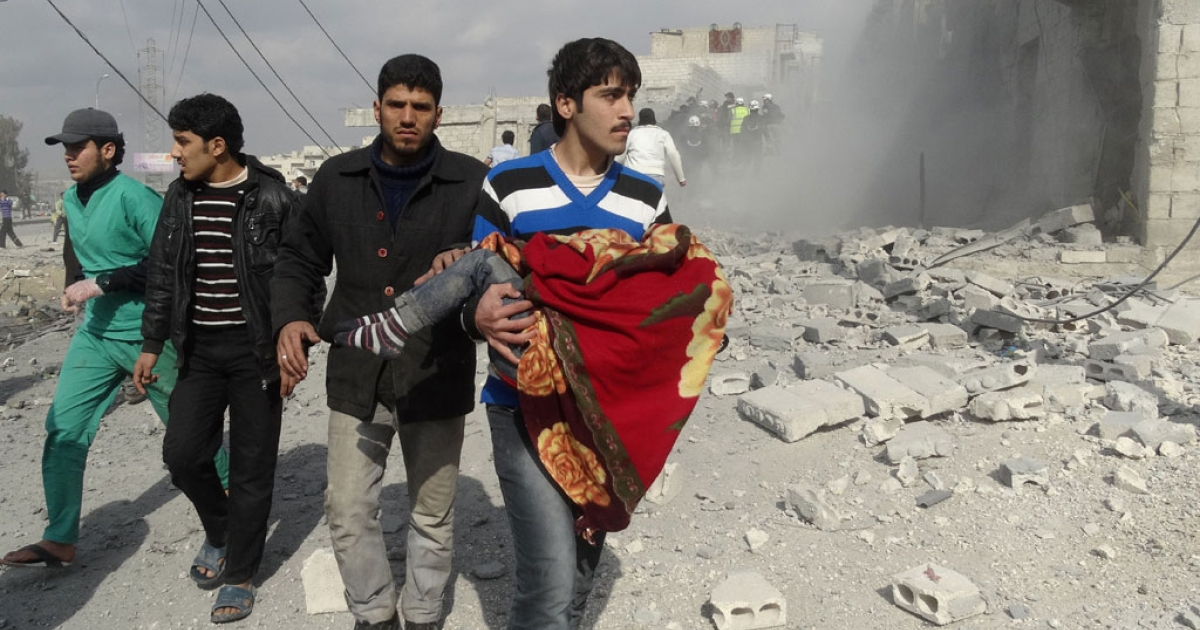 A Syrian man carries a body following a reported air strike by government forces on the al-Haidarya neighborhood of the northern city of Aleppo on Feb. 11, 2014.</p>
