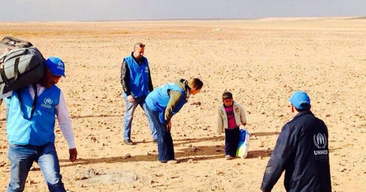 Marwan, a 4-year-old Syrian refugee, is assisted by UNHCR staff as he crosses the desert that straddles the Syrian border with Jordan. He had been temporarily separated from his family as they tried to flee the violence in Syria. UNHCR posted this image on Feb. 16.</p>