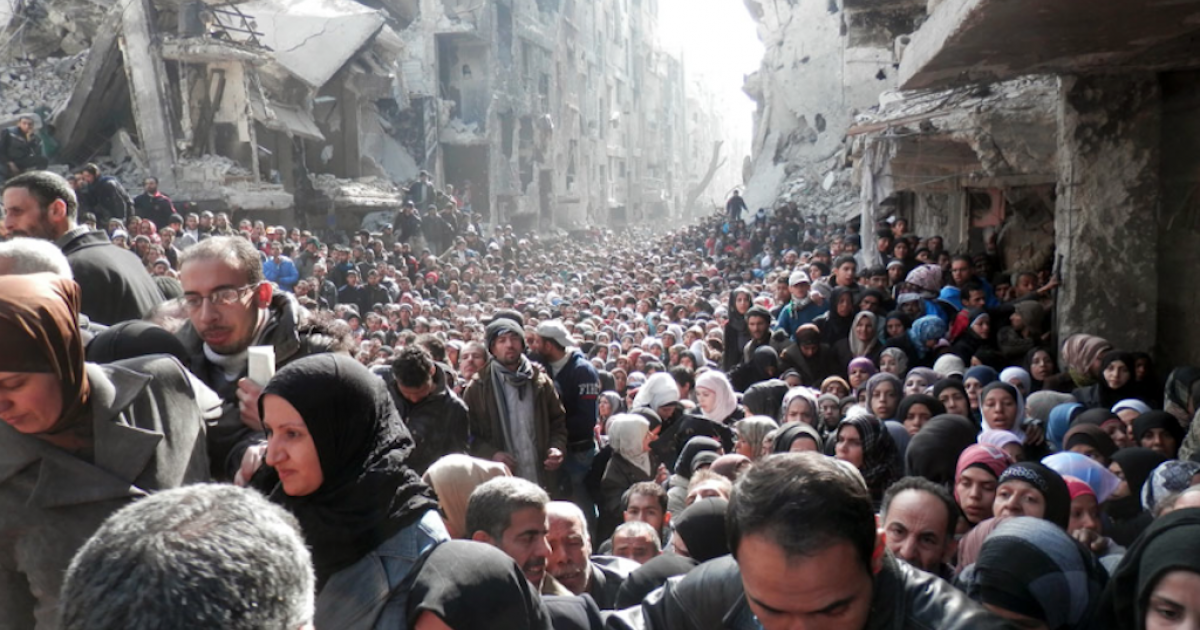 This photo released Wednesday by the UN agency for Palestinian refugees, the UNRWA, shows thousands of men, women and children trapped in the Yarmouk refugee camp on the outskirts of Damascus besieging aid workers as they distribute food parcels.  Photo courtesy of UNRWA.</p>