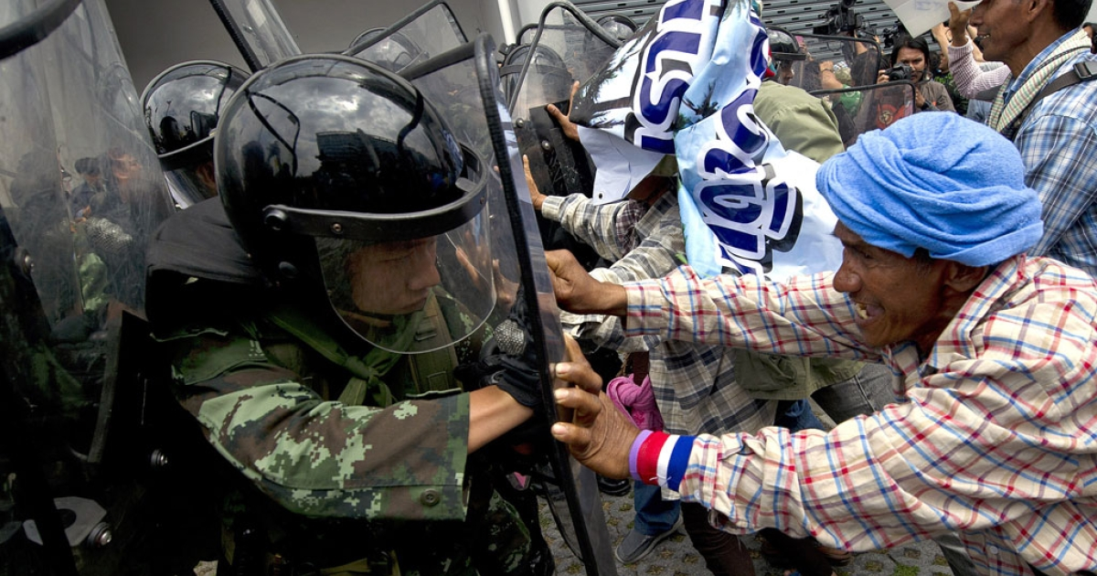 Thai farmers battle with soldiers as they protest the government's repeatedly delayed payments for rice at the government's temporary office in Bangkok on Feb. 17, 2014.</p>