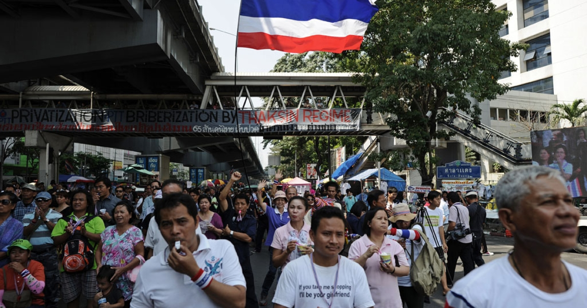Thai anti-government protesters listen to a leader's speech during a rally at a protest site in downtown Bangkok on February 4, 2014.</p>