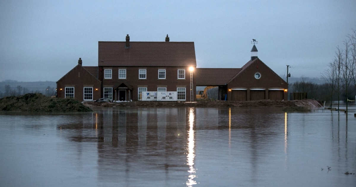 Rising flood waters surround a house in the village of Moorland on the Somerset Levels near Bridgwater, England.</p>