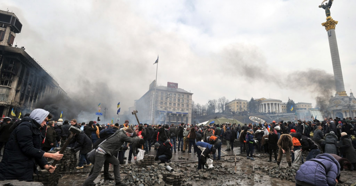 Anti-government protesters dig up cobblestones to use them as rocks against riot police on Kyiv's Independence square on Feb. 19, 2014</p>