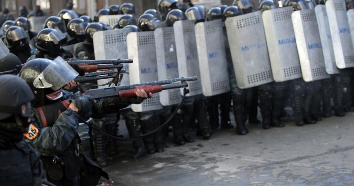 Riot police aim at anti-government protesters during clashes in central Kiev on Feb. 18, 2014</p>