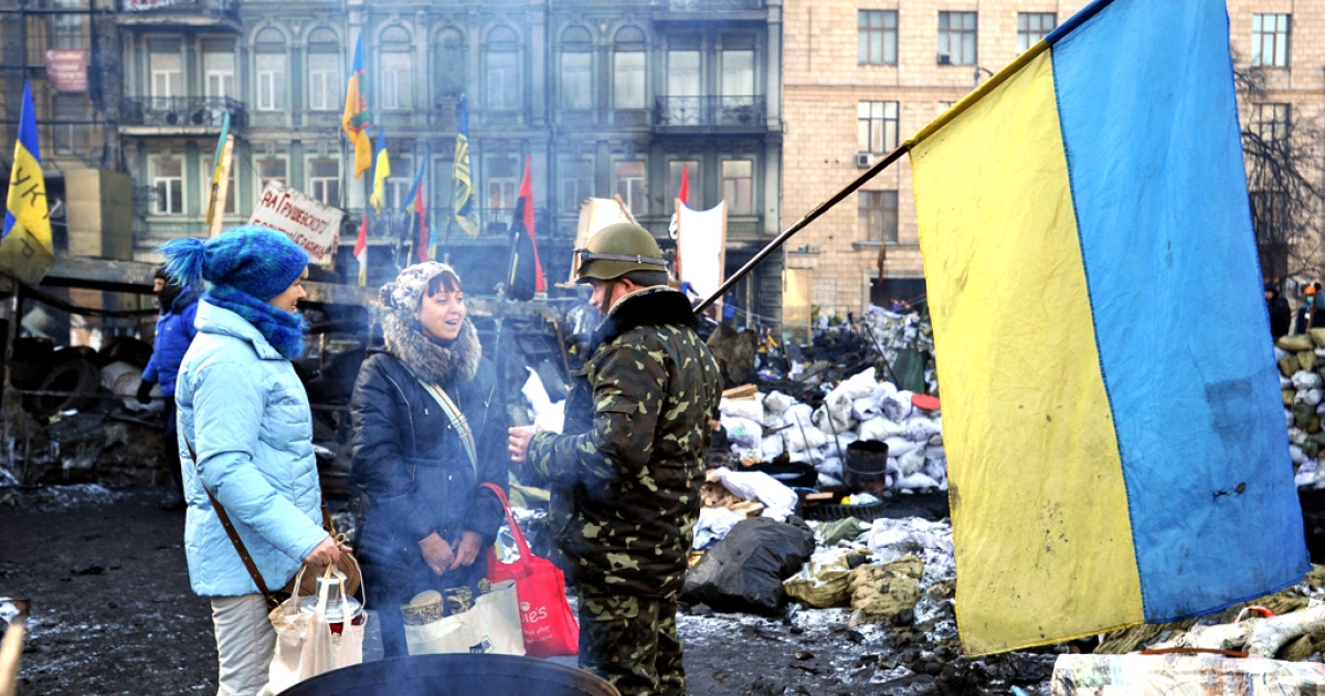 An anti-government protester holds a Ukrainian flag as he talks to women at a barricade on Grushevsky street in Kiev, on February 4, 2014.</p>