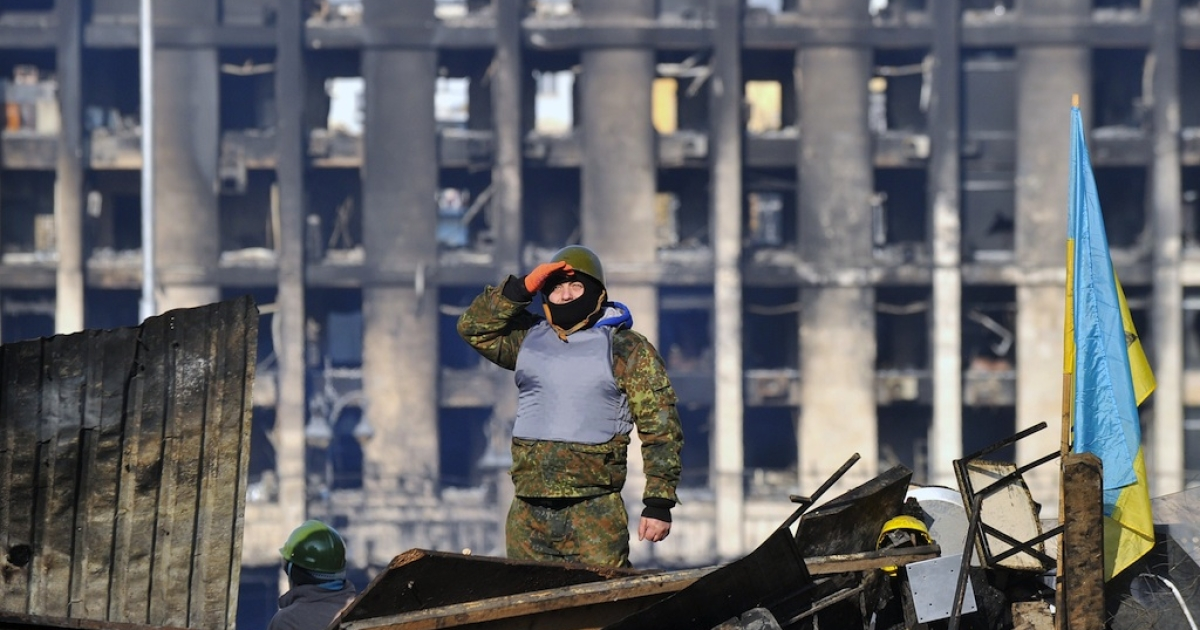 A protester stands on a barricade in front of the remains of the Trade Union building on Kyiv's Independence Square after Ukraine's deputy army chief resigned in protest on Feb. 21, 2014. On Saturday, the Interior Ministry transferred their support to the people of Ukraine as parliament considered impeaching President Yanukovych, who has left the capital.</p>