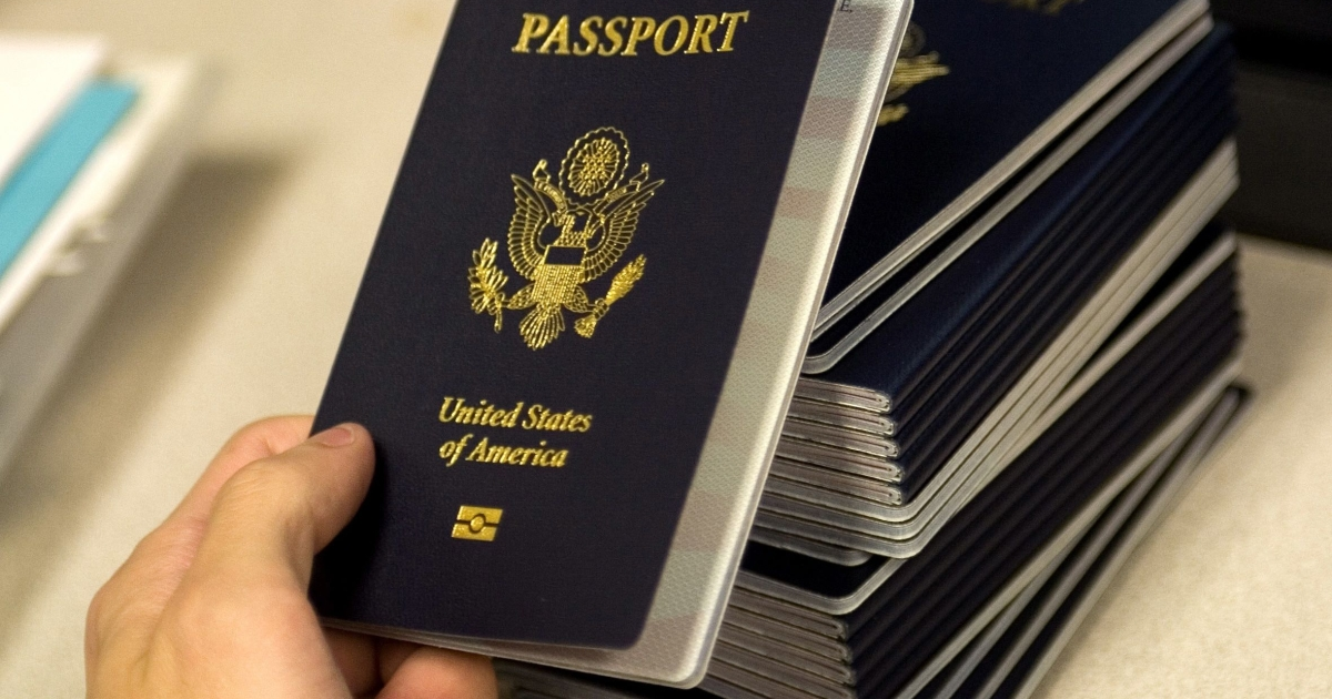 A US government official with the State Department's Passport Services reaches for a new blank US passport with an embedded electronic chip to begin the process of entering personal data and the photograph of an applicant.</p>