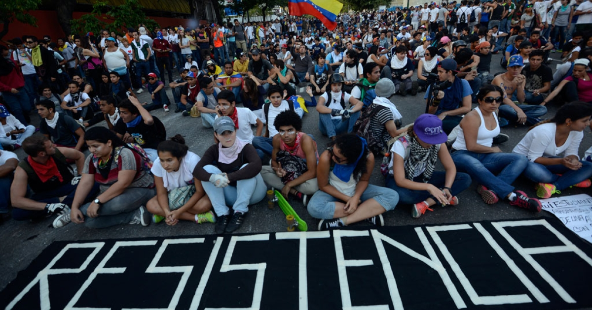 Anti-government students holding a protest sit on the street in Caracas on Feb. 16, 2014.</p>