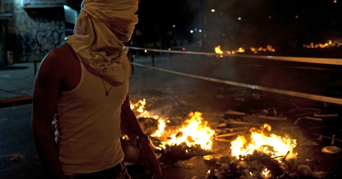 A Venezuelan protester lights a fire during clashes with riot police in Caracas on Feb. 20.</p>