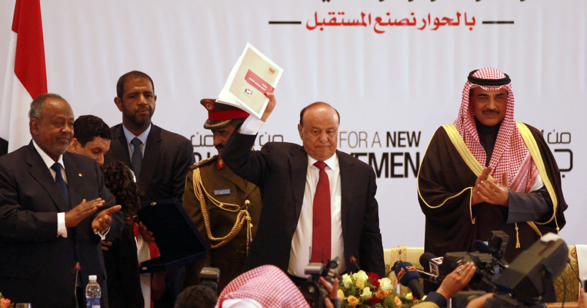 Yemen's President Abd-Rabbu Mansour Hadi (C) shows the book of the national dialogue at the end of a conference aimed at drafting a new constitution and establishing a federal state on Jan. 25, 2014 in Sanaa.</p>
