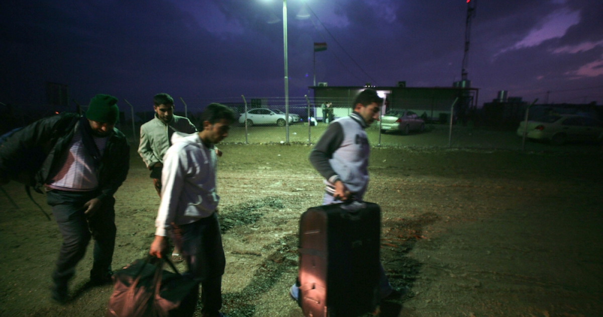 Syrian-Kurdish refugees carry their luggage a they arrive at the Domiz refugee camp, 20 km southeast of the northern Iraqi city of Dohuk, on November 10, 2012.</p>