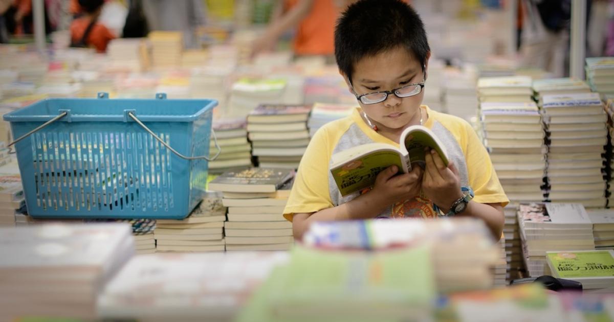 A boy reads a book at the Hong Kong Book Fair on July 17, 2013.</p>