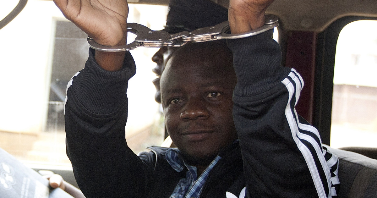Pika Manondo, one of the suspects implicated in the shooting of Malawi's Budget Director, waves his handcuffed hands as he leaves the Lilongwe Chief Resident Magistrate Court in a police vehicle, on November 11, 2013.</p>